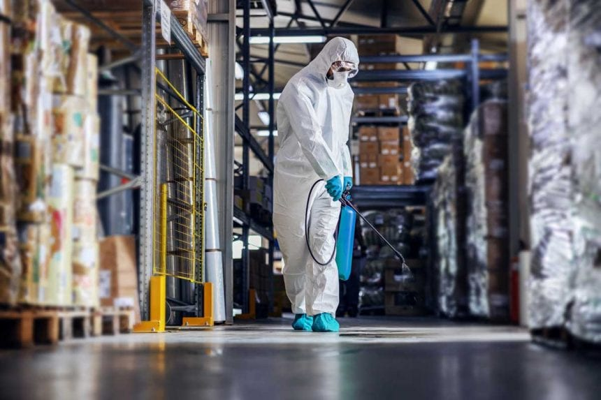 Man in protective suit and mask disinfecting warehouse